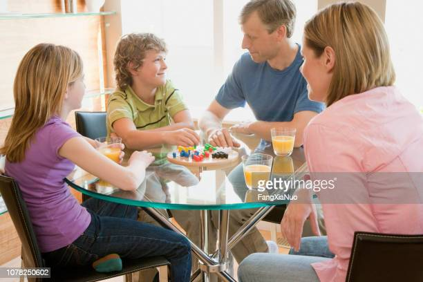 family playing game at home on table - sports round stock pictures, royalty-free photos & images