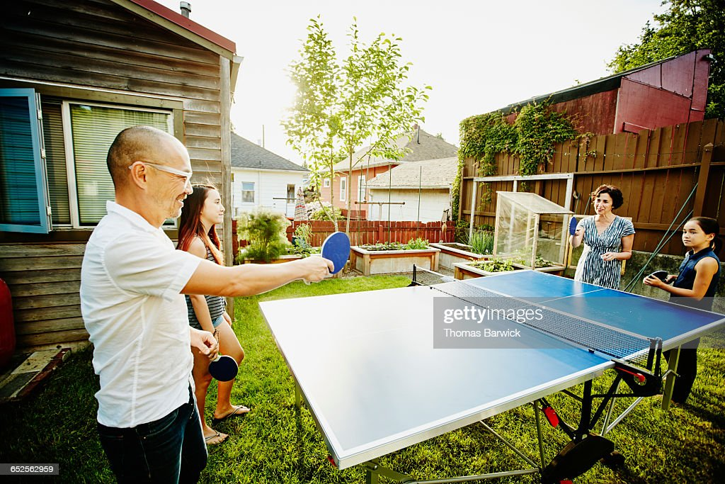Family playing game of ping pong in backyard : Stock Photo
