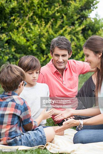 Family playing hand games together at picnic