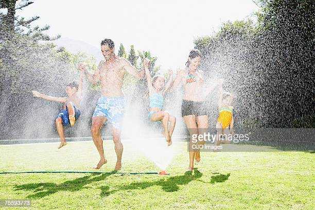 A family playing in a sprinkler