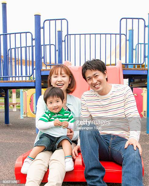 family playing in amusement park - 遊園地の乗り物 ストックフォトと画像
