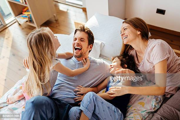 family playing in bed - family with two children stock photos and pictures