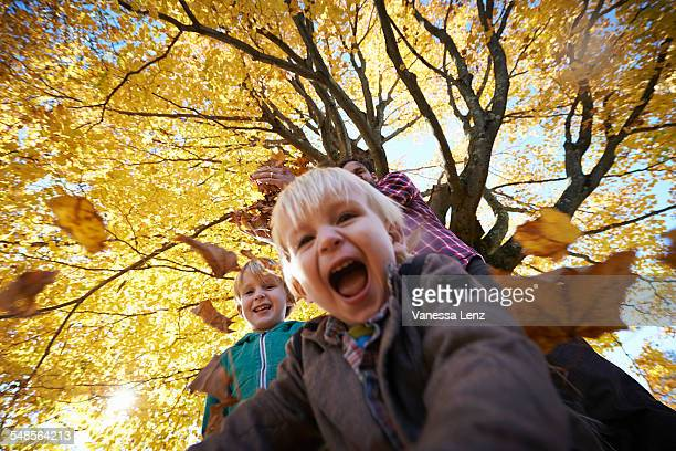 Family playing in forest, throwing leaves