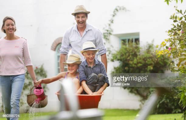 Family playing in garden with children in wheelbarrow