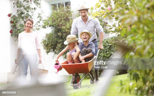 Family playing in garden with children in wheelbarrow
