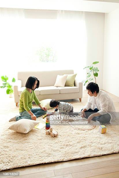 family playing in living room - three people ストックフォトと画像