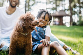 Family Playing In Park With Dog