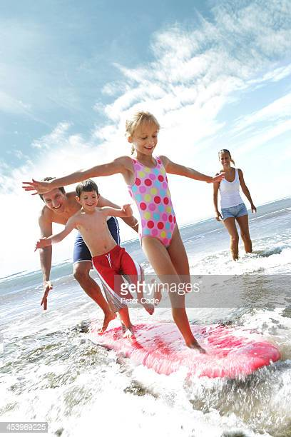 Family playing in sea with surfboard
