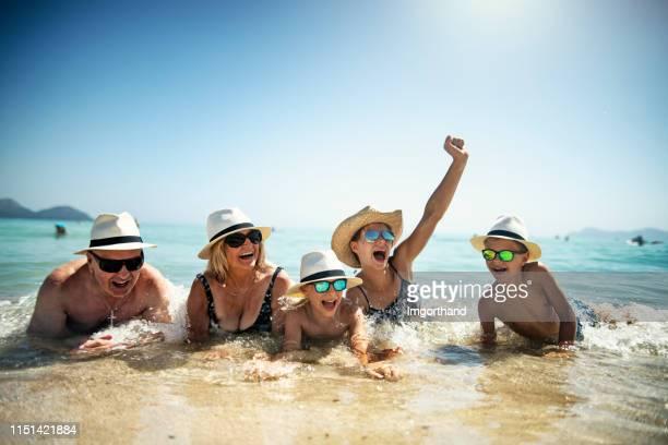 famille jouant dans les vagues de la mer méditerranée - vacances à la mer photos et images de collection