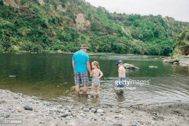 family playing in the water at a scenic river spot - seeufer stock-fotos und bilder