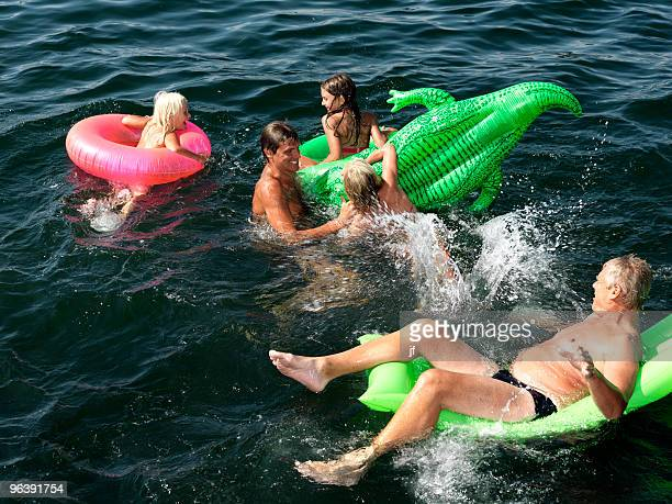 family playing in water - sea swimming stock photos and pictures