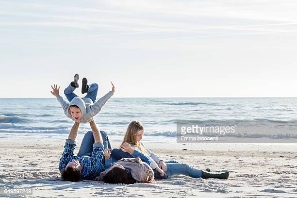 Family playing laying on the beach in winter