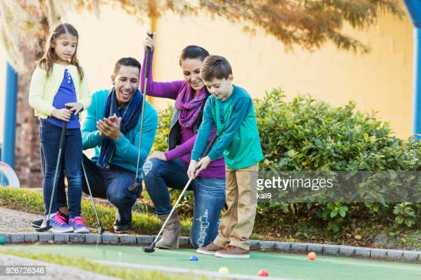 Family playing miniature golf, boy putting