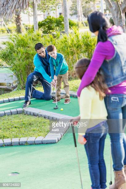 Family playing miniature golf, dad helping son