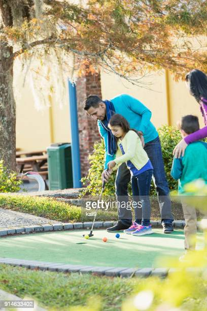Family playing miniature golf, father helping daughter