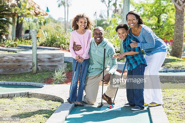 Family playing miniature golf