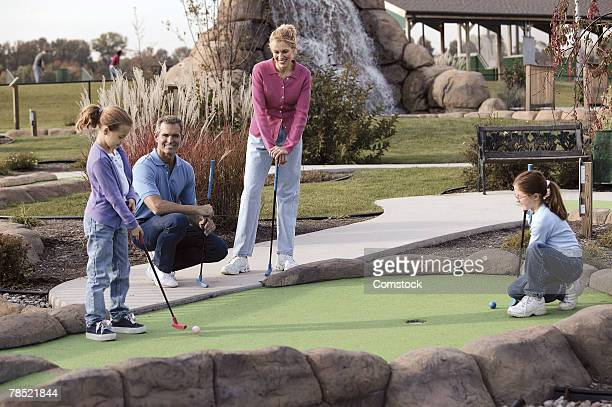 family playing miniature golf - miniature golf stock photos and pictures
