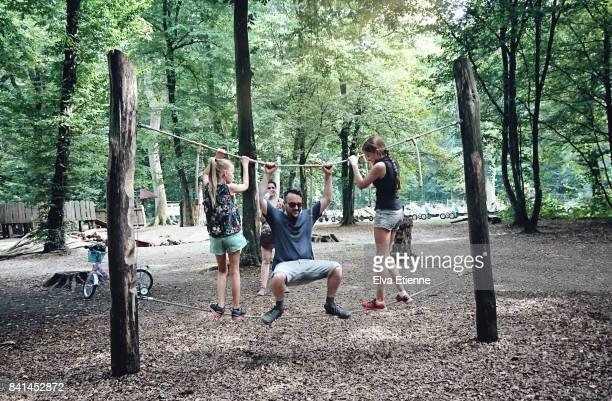 family playing on a balance rope in a forest park - kinderspielplatz stock-fotos und bilder