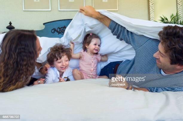 Familie spielt auf einem Bett.