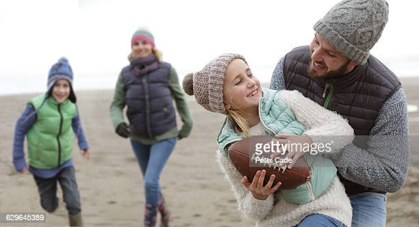 Family playing on beach in winter
