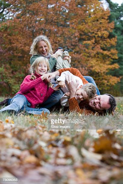 Family playing on grass in park in autumn