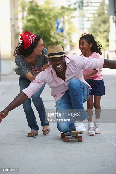 Family playing on skateboard on urban sidewalk