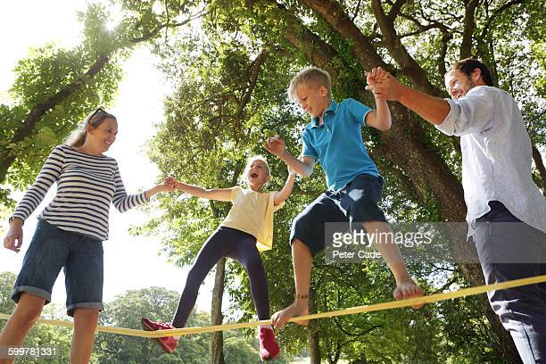 family playing on slackline in park