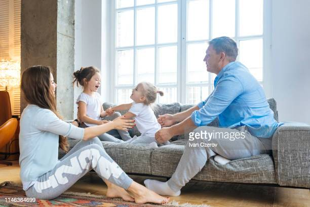 family playing on sofa - tracksuit bottoms stock pictures, royalty-free photos & images