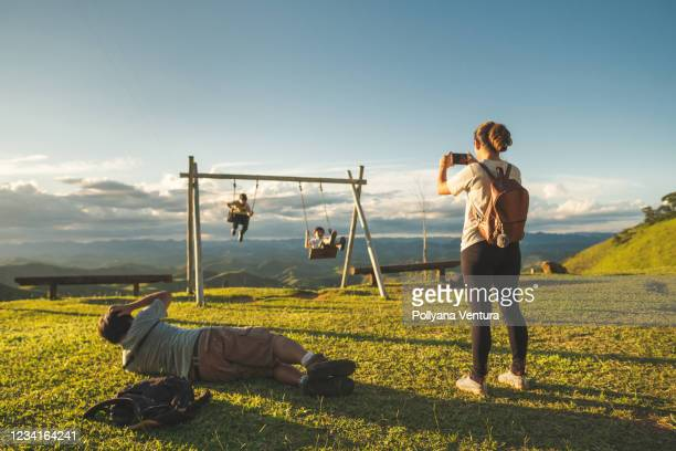 family playing on swing in nature park - hill range stock pictures, royalty-free photos & images