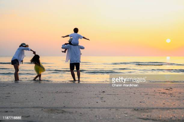 family playing on the beach - australia stock pictures, royalty-free photos & images