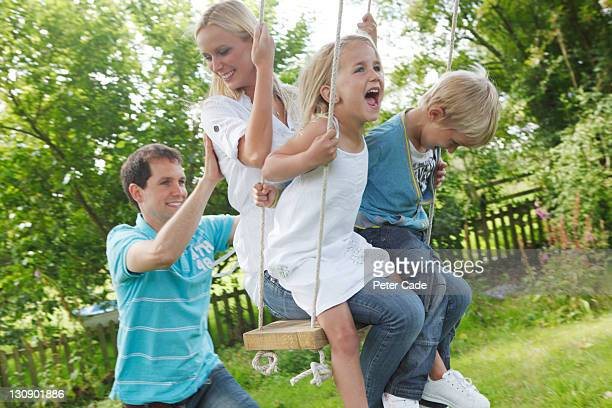 family playing on tree swing - mom sits on sons lap stock pictures, royalty-free photos & images