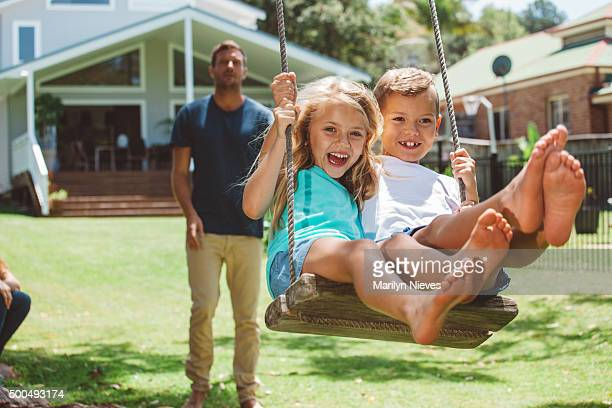 family playing outdoors - swinging stock pictures, royalty-free photos & images