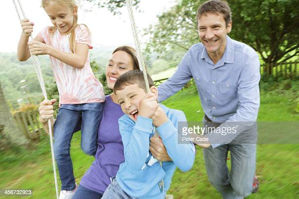 Family playing outside on tree swing