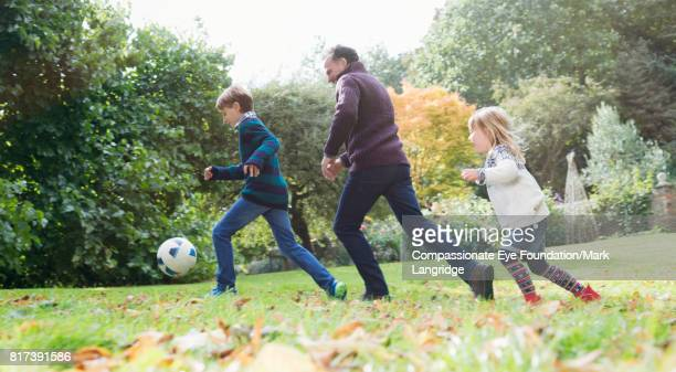 family playing soccer in backyard - football bulge stock photos and pictures