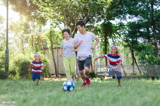 family playing soccer in public park - japan women football stock photos and pictures