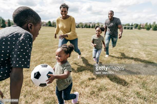 family playing soccer outdoor - life insurance stock pictures, royalty-free photos & images