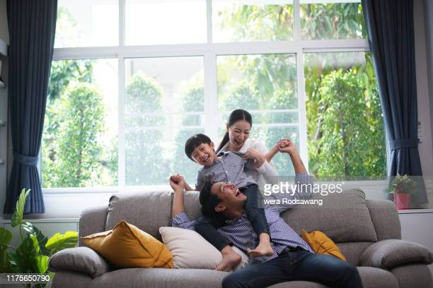 family playing together father giving his son piggyback ride happiness time together at home - asia stock pictures, royalty-free photos & images