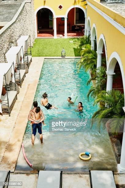 Family playing together in pool in courtyard of boutique hotel