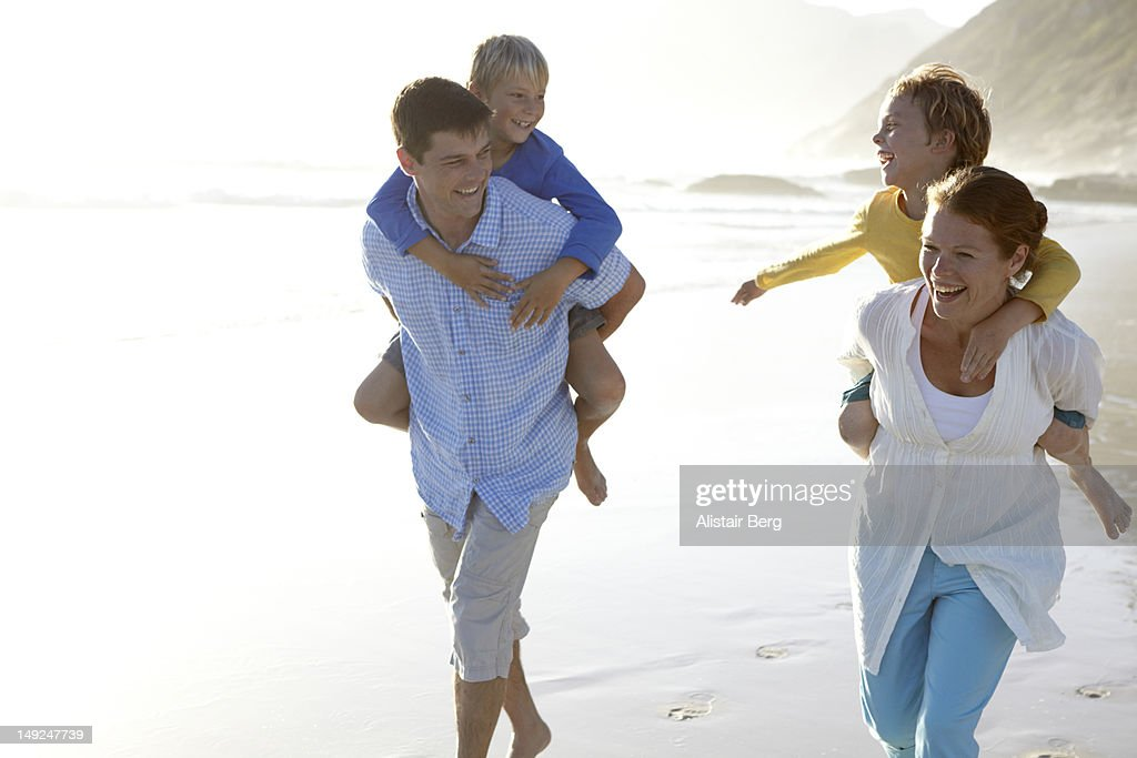 Family playing together on a beach : Stock Photo