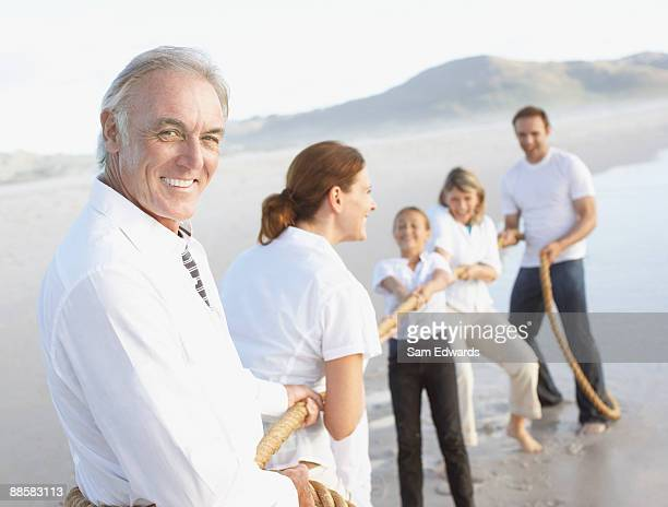 Family playing tug-of-war at beach