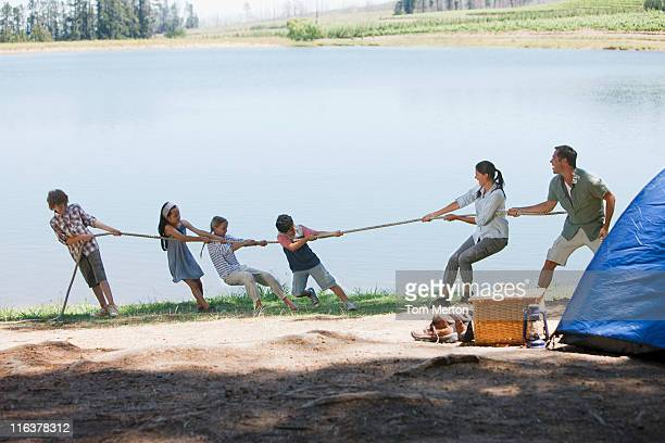 Family playing tug-of-war at campsite