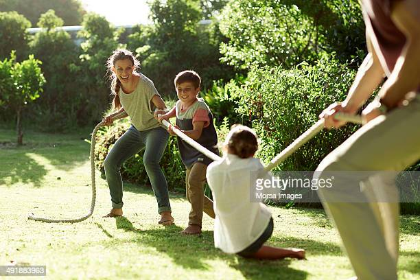 Family playing tug-of-war in park