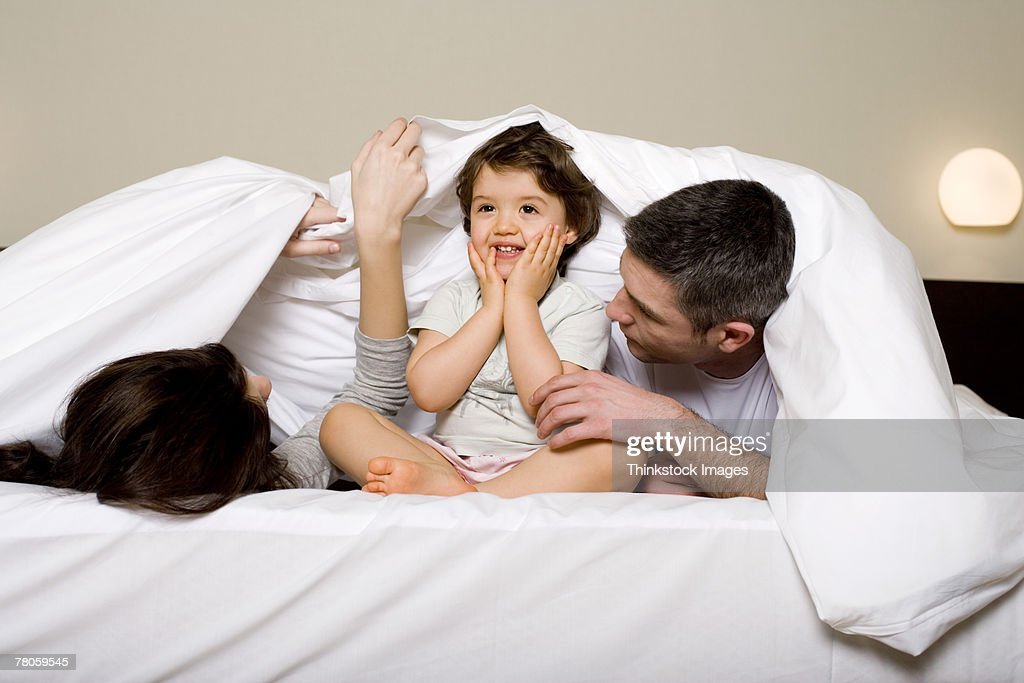 Family playing under bedspread : Stock Photo