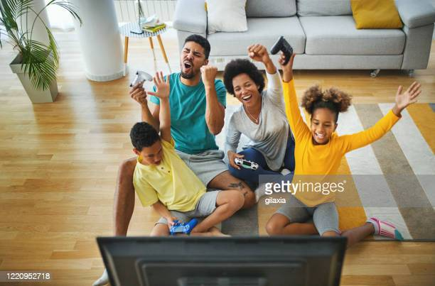 family playing video games at home during coronavirus quarantine. - illness prevention stock pictures, royalty-free photos & images