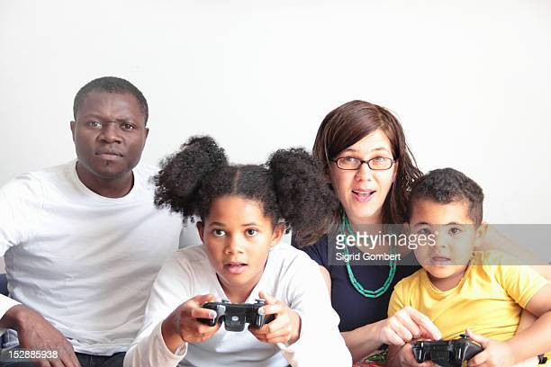 family playing video games together - sigrid gombert stock pictures, royalty-free photos & images