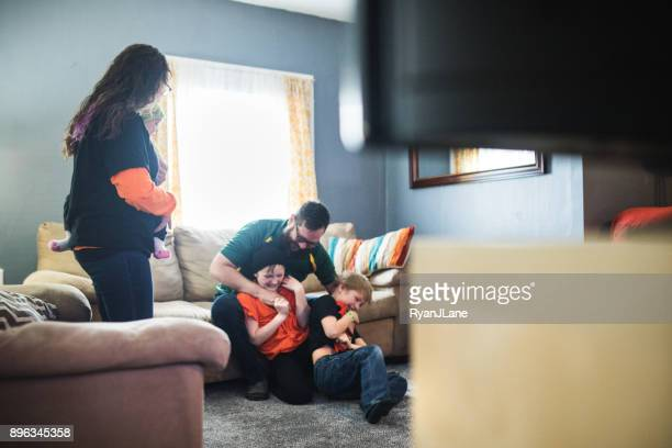 family playing while watching football game - girl wrestling stock pictures, royalty-free photos & images