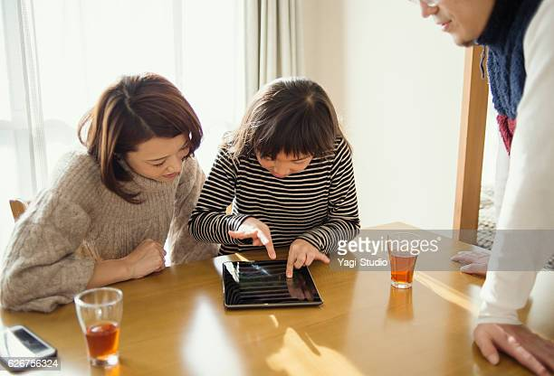 Family playing with a digital tablet in house