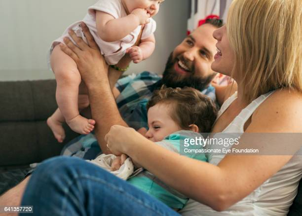 Family playing with baby girl on sofa