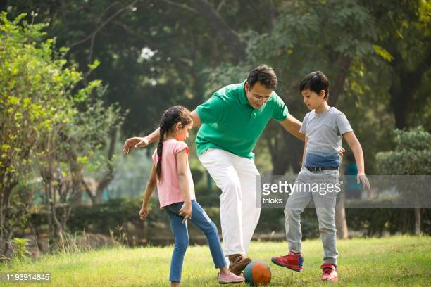 family playing with ball at park - sporting term stock pictures, royalty-free photos & images
