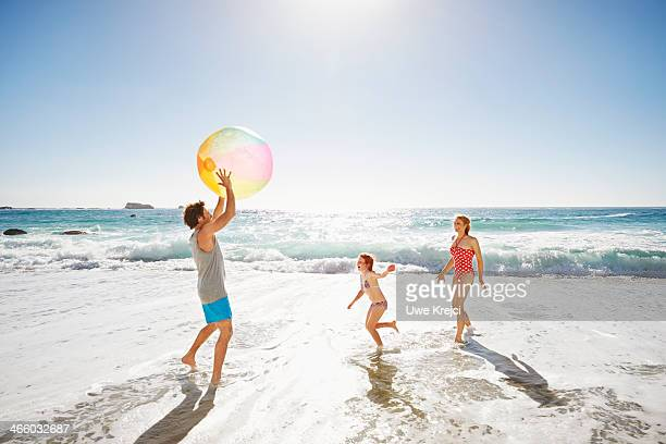 Family playing with ball by the ocean